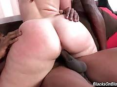 Big bottomed brunette rides one black dick and sucks another one.